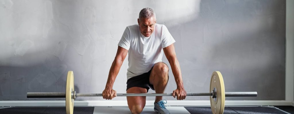 Mature man with weights at gym
